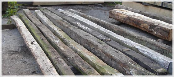 Reclaimed Oak Beams lying flat in the yard ready for delivery